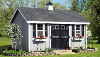 grey shed with cupola and newly planted tree to the left